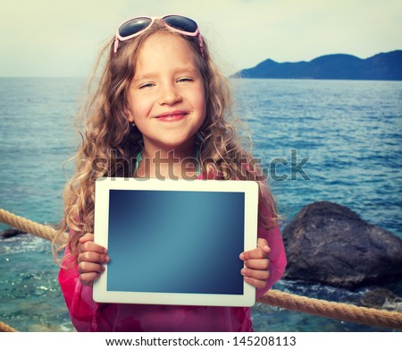 Child on the beach with tablet computer. Girl showing screen digital pc