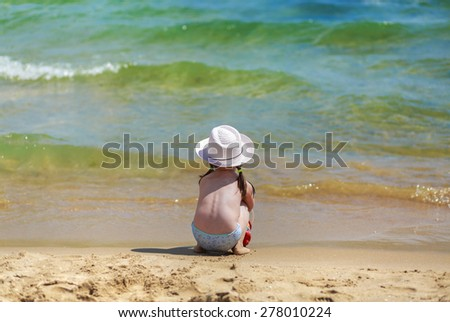Child on the coast of tropical sea. Baby sits with his back to the camera, looking at the waves. Shallow depth of field. Selective focus on the model. Space for text. - stock photo