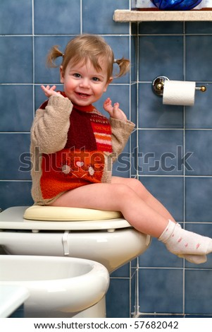 Child on the toilet - stock photo