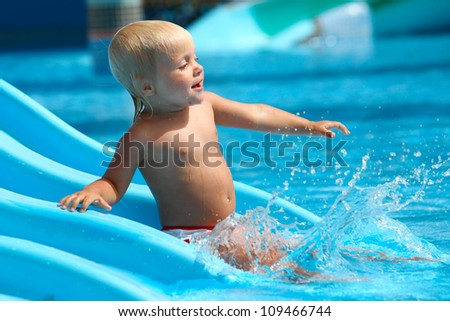 Child on water slide at aqua park.