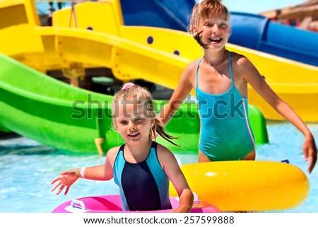 Child on water slide at aquapark. Blue bikini. - stock photo