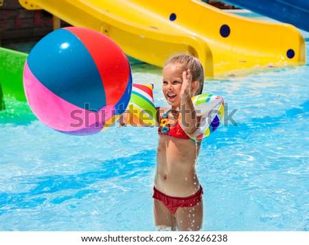Child on water slide at aquapark. Girl playing beach ball. Summer holiday. - stock photo