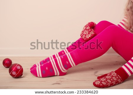 child on wooden floor with Christmas balls - stock photo