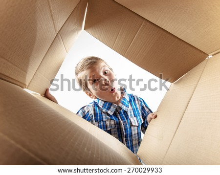 Child opening cardboard box and looking inside with surprise.