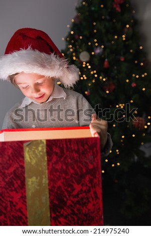 Child opening his christmas present with tree behind him - stock photo