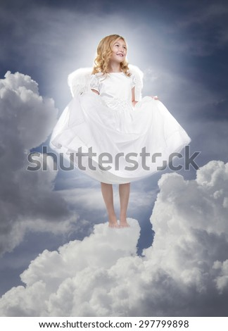 Child or girl angel wearing a white dress standing on fluffy clouds in the sky - stock photo