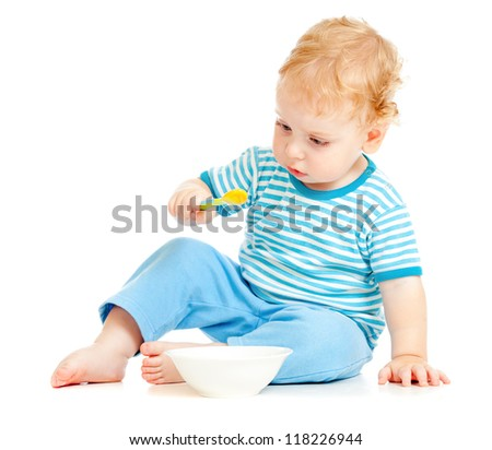 child or kid eating from plate with spoon - stock photo