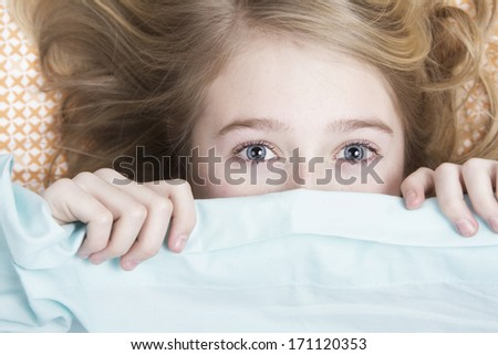 Child or teen hiding under covers in bed