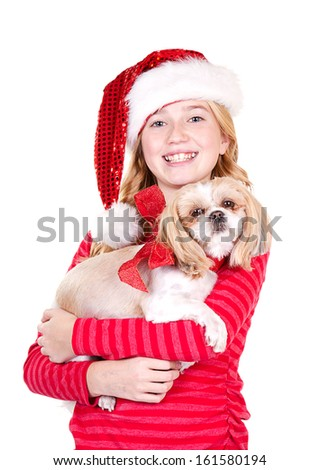 Child or teen holding a dog wearing a Santa hat on an isolated white background - stock photo