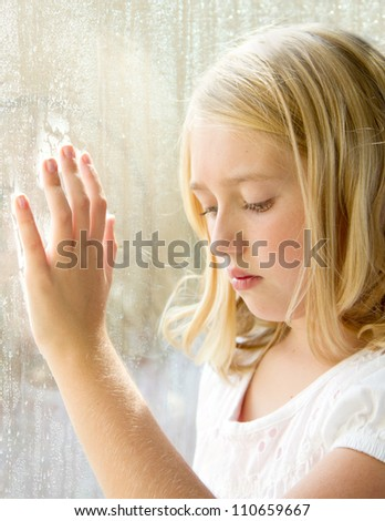 Child or teen looking down with hand on a rainy window