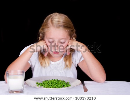 Child or teenager dislikes peas or vegetables, isolated on black