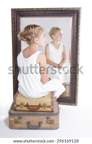 Child or young girl in front of a mirror, sitting on vintage luggage, with a fish tail braid in her hair. - stock photo