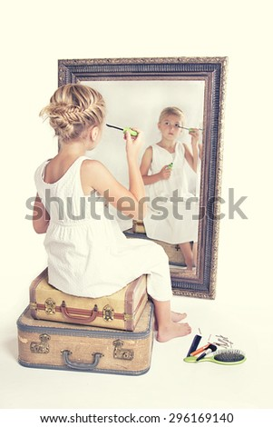 Child or young girl putting on make-up while looking at herself in a mirror, sitting on vintage luggage, with a fish tail braid in her hair. Vintage or retro filter applied. - stock photo