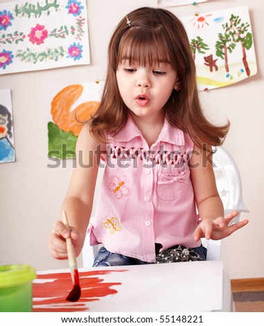 Child paint picture in preschool. Child care. - stock photo