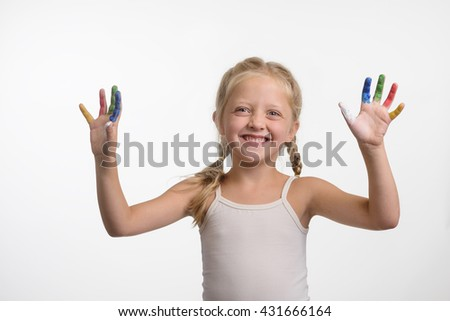 Child painted her fingers with paint of different colors. Little girl shows her hands to the camera with spread childish smile. Perfect retouching of the photo. - stock photo