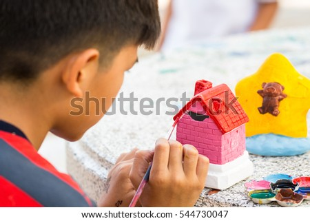 Child painting a ceramic pottery house model