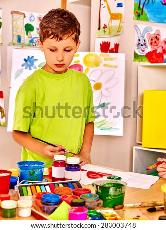 Child painting at easel in school. - stock photo