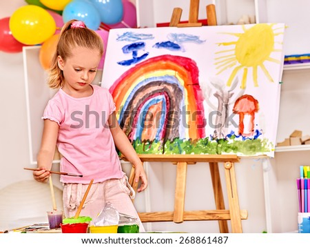 Child painting at easel in school. Education of small girl.