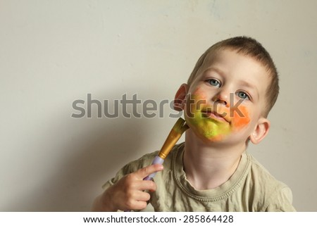 Child painting his face with aqua-color body painting with a brush - stock photo