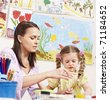 Child painting in preschool. Teacher help by little girl. - stock photo