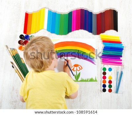 Child painting picture with brush in album using a lot of painting tools. Top view. Creativity concept. - stock photo