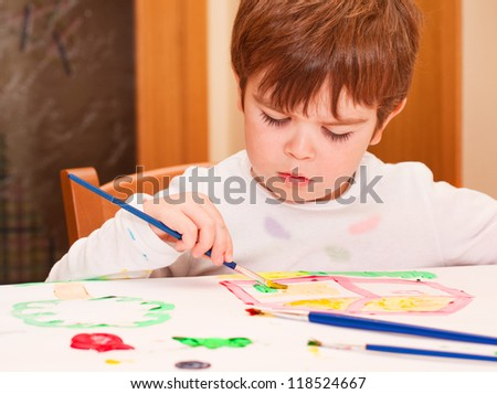 Child painting with brushes