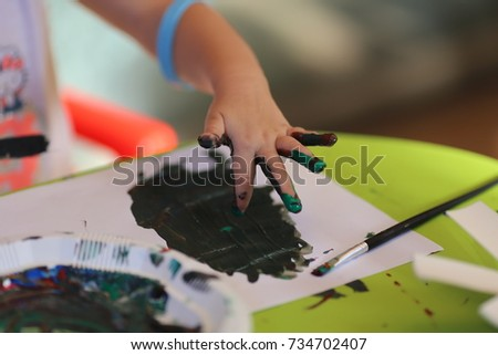 Child painting with her hand