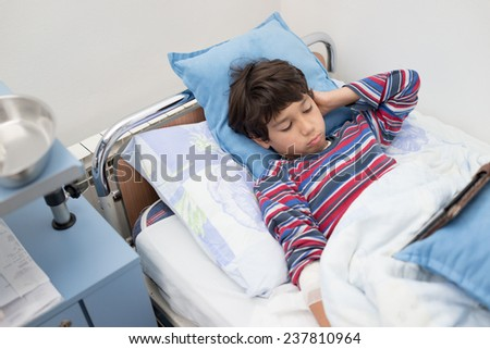 Child patient in hospital bed - stock photo