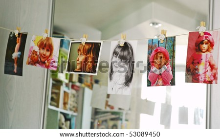 child photographs hanging on a clothesline in room