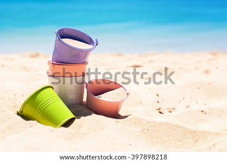 Child Play Colorful Buckets on Sand Beach Blue Sea Outdoor  - stock photo