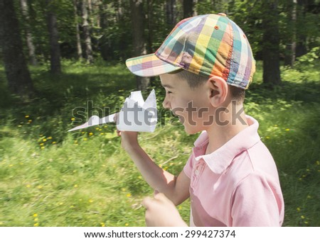 Child play with a stork made of paper. Forest - stock photo