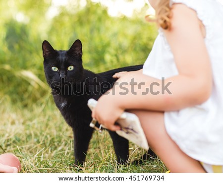 child play with black cat - stock photo