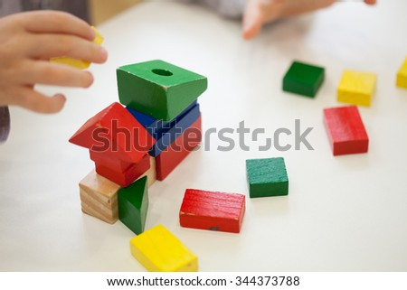 Child play with colored wooden brick shapes on white table. Close up view from above on hands and toys.