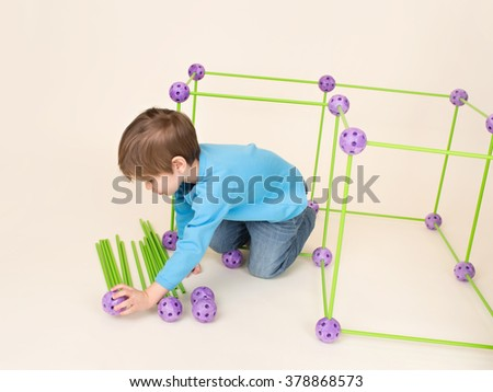 Child playing and building a fort or house using a construction set