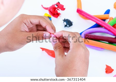 Child playing and creating toys from play dough. Child molding modeling clay. Strengthen the imagination of child. - stock photo