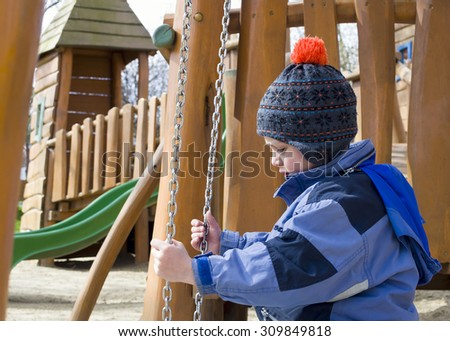 Child playing at children playground with modern wooden equipment on a cold day