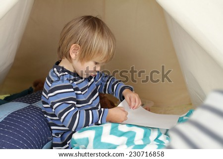 Child playing at home in a tent, drawing and art activity, showing a blank page - stock photo