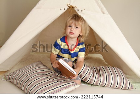 Child playing at home indoors with a teepee tent - stock photo