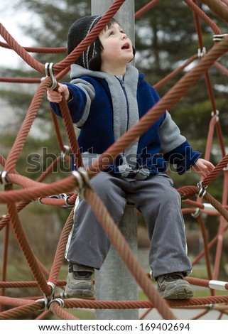 Child playing at playground on a climbing rope frame.  - stock photo