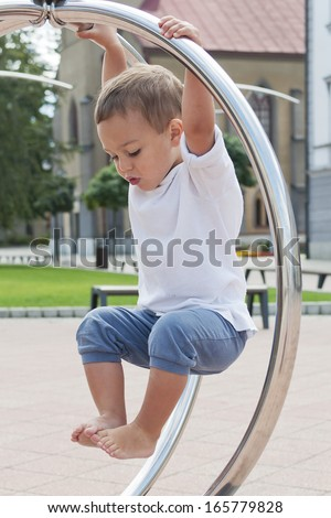 Child playing at urban playground hanging on climbing frame.  - stock photo