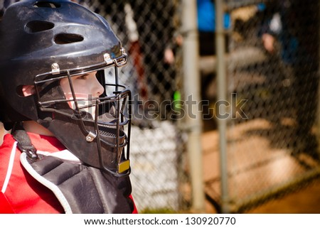 Child playing catcher during baseball game with space for copy - stock photo