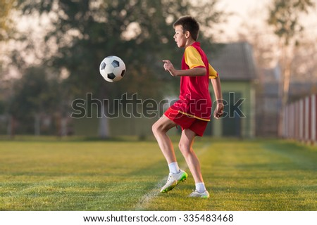 Child playing football on a soccer field - stock photo