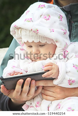 child playing game on the smart phone in mother hands