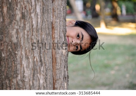 Child playing hide and seek. Cute little girl hiding behind huge tree. - stock photo