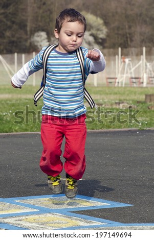 Child playing hopscotch game and jumping from number to number. - stock photo