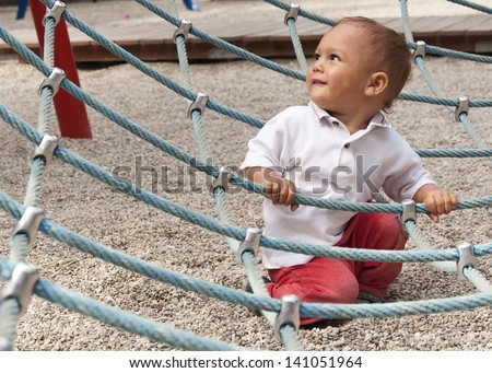 Child playing in playground on a modern rope climbing equipment.