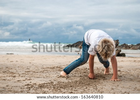 Child playing in sand on the beach