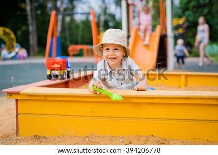 child playing in the sandbox - stock photo