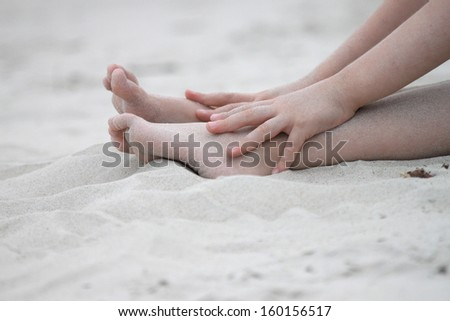 Child playing in white beach sand
