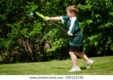 Child playing lacrosse at park - stock photo